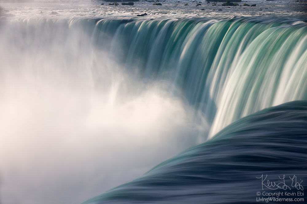 A thick cloud of mist forms in the curve of Horseshoe Falls, one of the waterfalls that make up Niagara Falls on the border of New York and Ontario. About 90 percent of the water in the Niagara River flows over Horseshoe Falls, which amounts to about 600,000 gallons (2.3 million liters) of water per second. The waterfall is about a half-mile wide, with a brink length of 2600 feet (792 meters), and it is 167 feet (51 meters) high. Horseshoe Falls is also known as Canadian Falls, since about two-thirds of it is located in Canada. It is pictured here from the Canadian side.