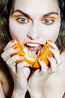 studio portrait of a beautiful woman holding orange mandarine citrus fruit
