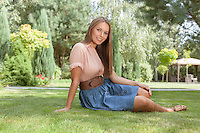 Full length portrait of beautiful young woman in casuals relaxing in park