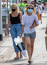 © Licensed to London News Pictures. 23/07/2020. London, UK. Shoppers in Chelsea wear masks while shopping on the Kings Road before it becomes compulsory in shops in England tomorrow. Face masks will be compulsory in shops, takeaway cafes and supermarkets from 24th July and enforced by the Police, with anyone who fails to wear one liable to a £100 fine. Photo credit: Alex Lentati/LNP