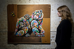 "© Licensed to London News Pictures. 24/05/2018. LONDON, UK. London, UK.  24 May 2018. An assistant views a painting of a polar bear at the preview of ""Missing"" an exhibition by artist and environmentalist Louis Masai at the Crypt Gallery in Euston.  The exhibition features sculptures, installations and paintings depicting 20 endangered species across the world from the South African penguin to the humble bumble bee.  The show runs 25 to 27 May 2018. Photo credit: Stephen Chung/LNP"