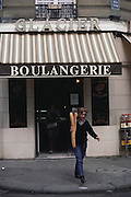 Antoinette Boulat leaves a bakery with two bagettes. Paris, France. MODEL RELEASED.