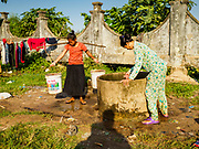 "15 FEBRUARY 2019 - SIHANOUKVILLE, CAMBODIA:  Women collect water from a well in a migrant camp in Sihanoukville. Families who live in the shanty town came to Sihanoukville from other Cambodian provinces because of the town's booming economy and construction industry building Chinese resorts and casinos. There are about 80 Chinese casinos and resort hotels open in Sihanoukville and dozens more under construction. The casinos are changing the city, once a sleepy port on Southeast Asia's ""backpacker trail"" into a booming city. The change is coming with a cost though. Many Cambodian residents of Sihanoukville  have lost their homes to make way for the casinos and the jobs are going to Chinese workers, brought in to build casinos and work in the casinos.      PHOTO BY JACK KURTZ"