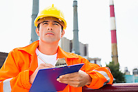 Male construction worker writing on clipboard at industry