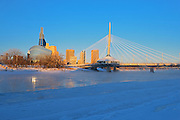 Winnipeg skyline with the Canadian Museum for Human Rights (CMHR) and the Esplanade Riel Bridge and the Red River in winter<br /> Winnipeg<br /> Manitoba<br /> Canada
