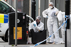 © Licensed to London News Pictures. 11/10/2019. Manchester, UK. Forensic scenes of crime examiners examine a bin at the foot of steps to the Arndale Centre on Exchange Square . Terrorism Police are investigating after four people were stabbed during a single attack at the Arndale Centre in Manchester City Centre . Photo credit: Joel Goodman/LNP