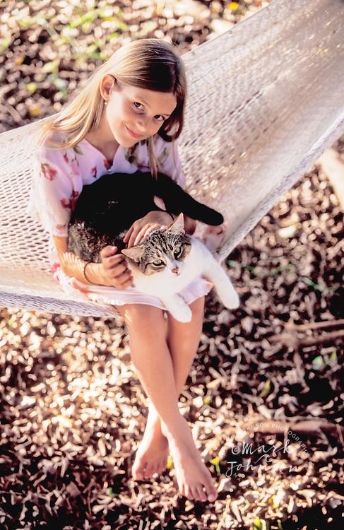 Hawaii, USA --- Girl on a Hammock holding a cat