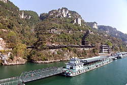 Extensive floating dockage to handle cruise passengers fronts a re-created traditional water village on the Yangtze River, a shore excursion for tourists cruising the river between Jingzhou and Chongqing. <br /> Visitors climb the covered stairway up to the village, a hefty hike.