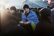 Anti-government protesters in a food distribution line as they occupy Maidan Square defended with barricades against police and government supporters incursions, on December 9, 2013 in Kiev, Ukraine. Thousands of people have been protesting against the government since a decision by Ukrainian president Viktor Yanukovych to suspend a trade and partnership agreement with the European Union in favor of incentives from Russia was made recently.
