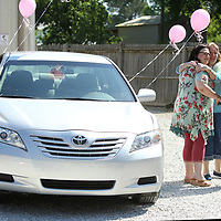 "Donna Clingan, center, of Pontotoc, hugs her daughter-in-law Brandy Clingan, as they talk with with Donna's son Matthew, while standing next to the 2009 Toyota Camry that was awarded to Donna Friday morning at McCord's Auto Service in Belden. NAPA AutoCare Center of Northeast Missisippi hosted the ""mother"" of all giveaways in celebration of mom this Mother's Day. Donna was nominated by her daughter-in-law Brandy Clingan who wrote a short survey describing Donna's selfless contribution to her community and family."