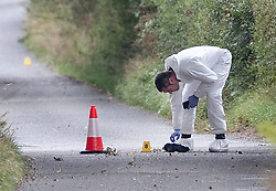 © Licensed to London News Pictures. 16/08/2019. Sulhamstead, UK. A forensic officer examines a piece of cloth in Lambdens Hill near Sulhamstead, Berkshire, where a police officer was killed while investigating a suspected burglary. Ten people have been arrested on suspicion of murder including a 13-year-old child. Photo credit: Peter Macdiarmid/LNP