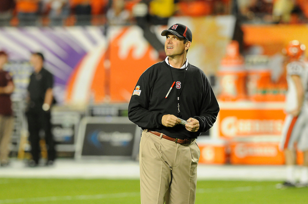 January 3, 2011: Head coach Jim Harbaugh of the Stanford Cardinal watches his team warm up prior to the the NCAA football game between the Stanford Cardinal and the Virginia Tech Hokies at the 2011 Orange Bowl in Miami Gardens, Florida.