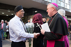 © Licensed to London News Pictures. 25/3/2016. Birmingham, UK. Good Friday Walk of Witness. Churches in Birmingham come together to walk through Birmingham City Centre, visiting Cathedrals and Churches.<br /> Pictured, Archbishop Bernard Longley (right) receives flowers from local shopkeepers on New Street. Photo credit : Dave Warren/LNP
