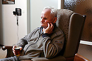 elderly man relaxed watching television with a beer