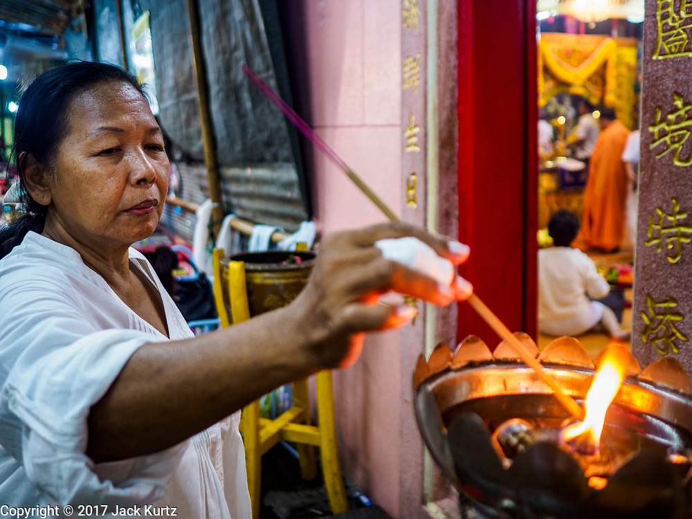 20 OCTOBER 2017 - BANGKOK, THAILAND: A woman lights incense Chit Sia Ma Shrine in Bangkok's Chinatown on the first day of the Vegetarian Festival, what Thais call the Taoist Nine Emperor Gods Festival, in the Chinatown neighborhood of Bangkok, Thailand. It is a nine-day Taoist celebration beginning on the eve of 9th lunar month of the Chinese calendar. For nine days people participating in the festival wear only white and don't eat meat, poultry, seafood, and dairy products. The vegetarian festival is celebrated throughout Thailand, but especially in Phuket and Bangkok, cities with large ethnic Chinese communities.       PHOTO BY JACK KURTZ
