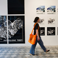 "VENICE, ITALY - JUNE 04:  A woman walks in front of prints at  ""The Pavillion Tibet"" a project by Ruggero Maggi on June 4, 2011 in Venice, Italy. The Venice Art Biennale will run from June 4 to November 27, 2011."