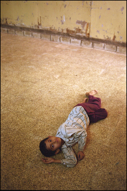 INDIA. Mumbai (Bombay). 2002. An eight-year old runaway child lies on the floor. The frightened boy had told social workers that he was working in a clothes factory and that he does not know where his family is.