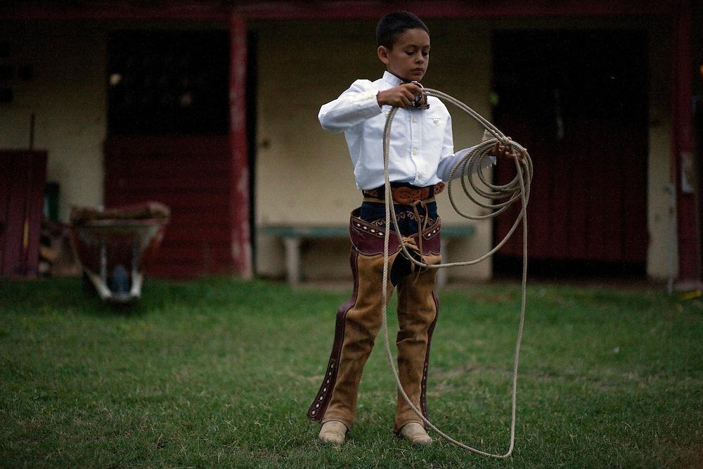"Edmundo Rios III, ""Mundito"", 14, practices with his lariat, or reata, after a charreada at the San Antonio Charro Ranch.  Mundito is a third generation charro."