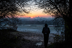 © Licensed to London News Pictures. 12/12/2017. London, UK. A walker stops to watch the sun rise over the city of London from Hampstead Heath on a freezing morning. Temperatures across the the UK dipped overnight with some regions expected to drop to -13C (9F). Photo credit: Ben Cawthra/LNP