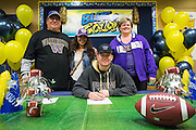 Jason Scempos and his family pose with a duplicate National Letter of Intent to play football at the University of Washington during the NCAA National Signing Day event at Milpitas High School in Milpitas, California, on February 4, 2015. (Stan Olszewski/SOSKIphoto)