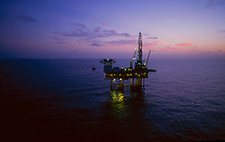 Stock photo of an offshore jack-up oil and gas drilling rig at sunset in the Gulf of Mexico, Texas