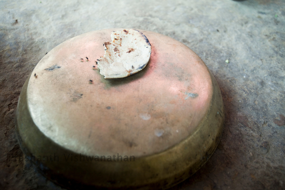 A fly ridden roti (wheat bread) lies around as 60 year old Pirbhu cooks food for his two sons he supports, as his elder two sons have migrated to cities for better oppurtunities due to drought in Pratappura Chattarpur Madhya Pradesh, India, on Wednesday September 9, 2009. The sons donot send any money home and Pirbhu does not get any employment under the National Rural Employment Guarantee Act (NREGA)  Photographer: Prashanth Vishwanathan/Action Aid