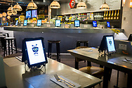 Multiple Apple iPads with advertisements on their screens wait at the ready for customers to sit at a restaurant in concourse G of the Minneapolis-St. Paul International Airport (MSP), Minnesota, USA.