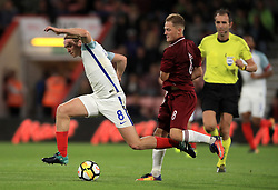 England's Tom Davies, (left) battles for possession of the ball with Latvia's Andrejs Ciganiks