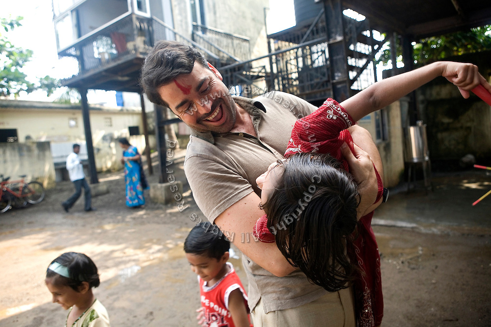 Jaume Sanllorente, the director general of Sonrisas de Bombay is playing with a child in the courtyard of a school run by the fast-growing Spanish NGO in Mumbai, India.
