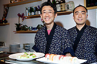 Portrait of happy Asian chefs with sushi in foreground