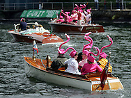 Members of a classic boat club are decked out in pink flamingo hats as they participate in the Opening Day boat parade held in conjunction with the annual Windermere Cup race Saturday in Seattle. (AP Photo/John Froschauer)