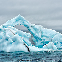 Iceberg with arch in Arctic Ocean north of Svalbard Islands.