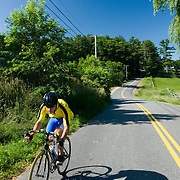 A male triathlete in a yellow shirt and blue pants speeds up a hill, on a sunny day.  2007 Shipbuilders Triathlon in Bath, Maine.