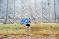 Jennifer Berlinger, member of the Andover Homeowners Association, holds a sign in front of a massive construction curtain during a Community Day of Resistance in protest of construction of the Mariner East 2 pipeline by Energy Transfer Partners