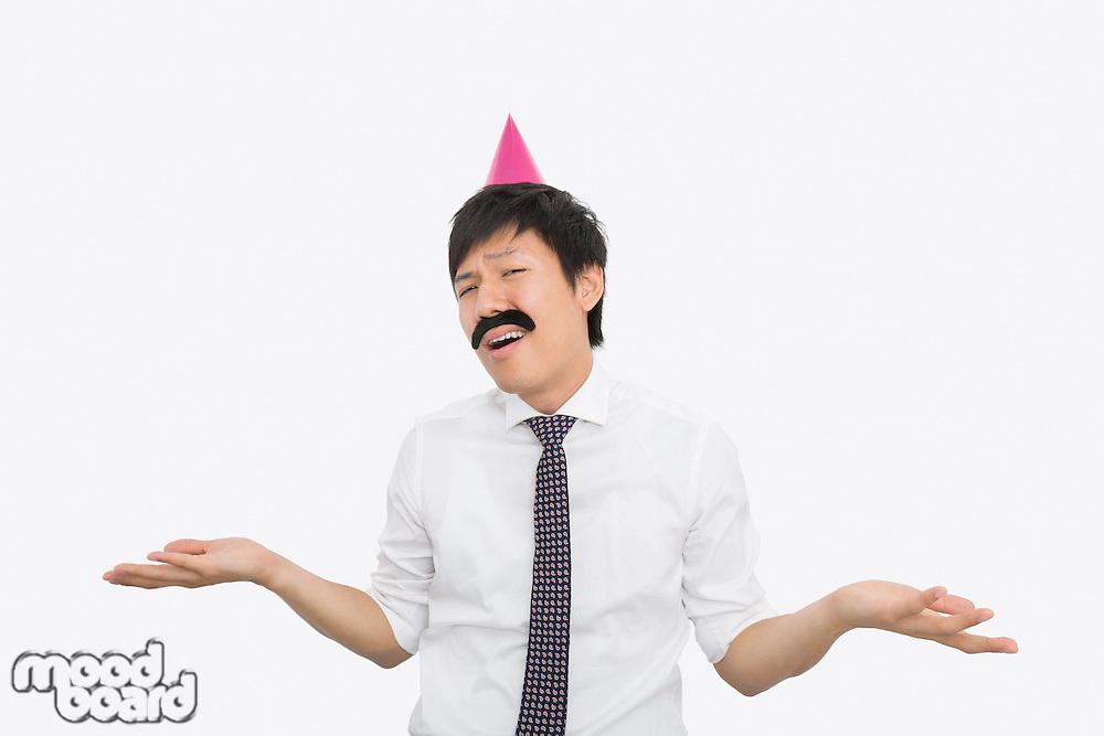 Mid adult businessman shrugging his shoulders over white background