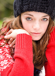 Close up of teenaged girl wearing woolly hat with face resting on hands