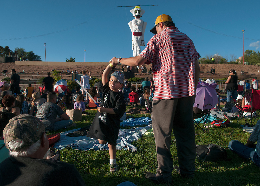 em082914o/a1/Zion Lucero, 5, dances with his uncle Daniel Roybal as they wait for the burning of Old Man Gloom. Thousands of people attended the 90th burning of Zozobra at Fort Marcy Park in Santa Fe, Friday August 29, 2014. (Eddie Moore/Albuquerque Journal)