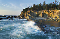 Surf pounding against sandstone cliffs of Shore Acres State Park on the Oregon Coast