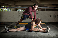 A male athlete offers assistance to a female athlete as she stretches as a part of warm up.