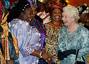 Queen of England Elizabeth II (R) shares a laugh with the Director General of the Nigerian stock exchange, Dr Noidi Okereke Onyiwke (L in purple) at a reception for the Queen at the State House in Abuja, Nigeria Wednesday 03 December 2003. The Queen of England, Elizabeth II, visited Nigeria in December 2003 which was the first state visit there since 1956.
