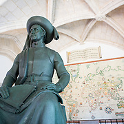 A statue of Henry the Navigator (1394-1460) that stands inside the entrace to the Museu de Marinha (Maritime Museum) in Lisbon, Portugal. Behind the statue, against the wall, is a large map tracing the major voyages of Portugal's Age of Discovery. The Museu de Marinha (Maritime Museum of Navy Museum) focuses on Portuguese maritime history. It features exhibits on Portugal's Age of Discovery, the Portuguese Navy, commercial and recreational shipping, and, in a large annex, barges and seaplanes. Located in the Belem neighborhood of Lisbon, it occupies, in part, one wing of the Jerónimos Monastery. Its entrance is through a chapel that Henry the Navigator had built as the place where departing voyagers took mass before setting sail. The museum has occupied its present space since 1963.