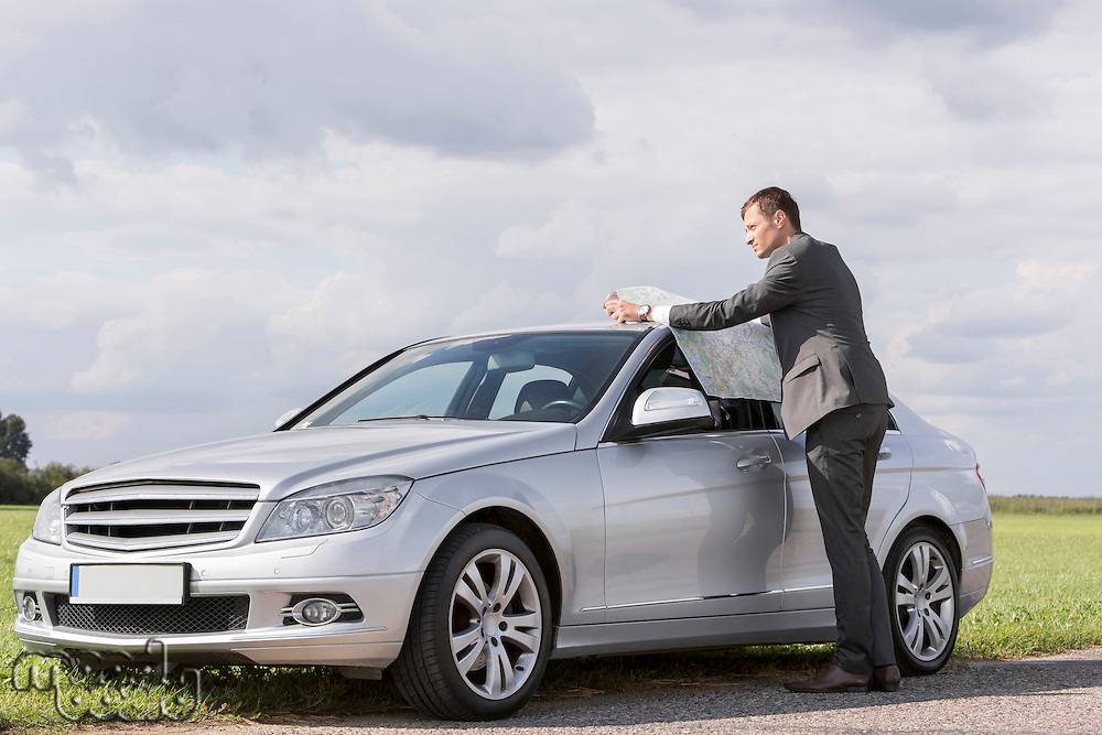 Full length of young businessman reading map by car at countryside