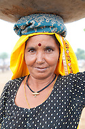Portrait of a mature Indian woman carrying a load on her head.