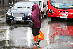 © Licensed to London News Pictures. 19/07/2019. London, UK. A woman covers her head with her jacket during rainfall in north London. Photo credit: Dinendra Haria/LNP