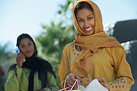 Two muslim woman, one with shopping bag