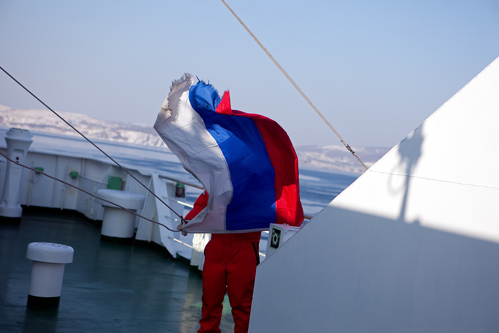 """Employee of the """"Eastern Dream"""" ferry running up the russian flag during arrival to the sea port of Vladivostok in Russia. Vladivostok, Russian Federation, Russia, RUS, 12.01.2010."""