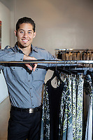 Portrait of a happy young man standing by clothes rack in fashion boutique