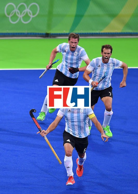 Argentina's Pedro Ibarra (bottom) celebrates a goal during the men's Gold medal field hockey Belgium vs Argentina match of the Rio 2016 Olympics Games at the Olympic Hockey Centre in Rio de Janeiro on August 18, 2016. / AFP / MANAN VATSYAYANA        (Photo credit should read MANAN VATSYAYANA/AFP/Getty Images)