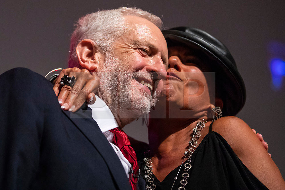 © Licensed to London News Pictures. 26/09/2018. Liverpool, UK. Labour Party Leader Jeremy Corbyn MP (L) is kissed on the cheek by a member of the Liverpool People's Choir on stage after his speech at the end of the Labour Party Conference. Photo credit: Rob Pinney/LNP