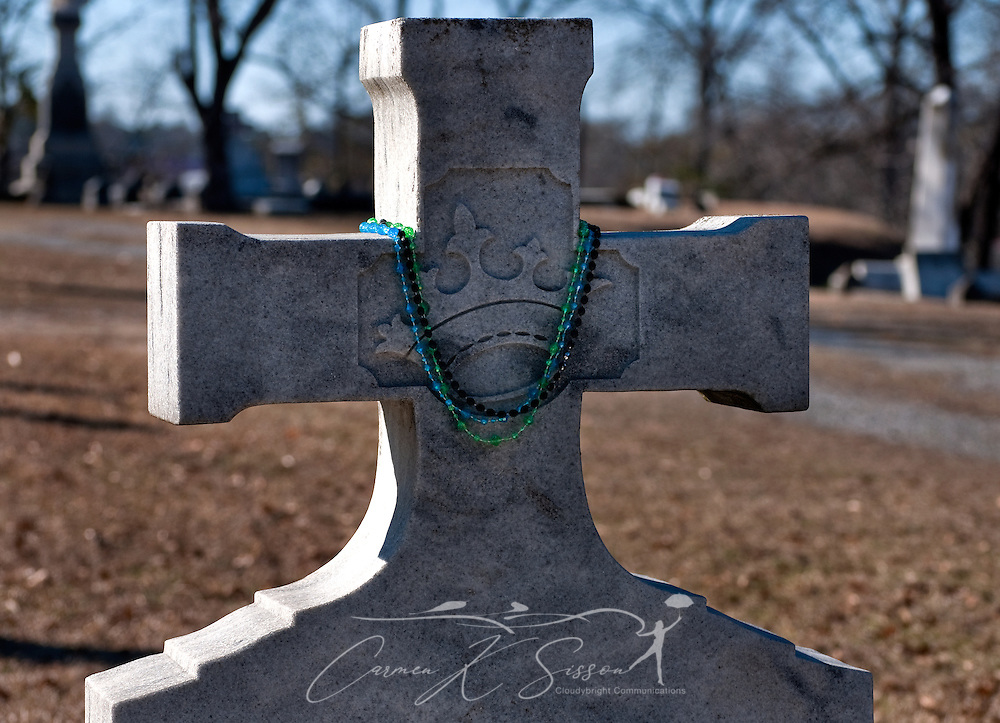 Mardi Gras beads decorate the headstone of Lawrence Mitchell at Rose Hill Cemetery in Meridian, Mississippi. Mitchell was a member of the Gypsy Royal Family, many of whom are buried nearby. Tourists and visitors often leave gifts of fruit, trinkets, and liquor on the family's graves. (Photo by Carmen K. Sisson/Cloudybright)